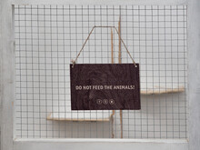 "A Warning Sign On The Background Of A Cage In A Zoo Or Nature Reserve:""Do Not Feed The Animals."" The Concept Of Protecting Animals From Improper Nutrition And Overeating. Green Movement."