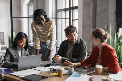 Multi-ethnic group of business people discussing project while sitting at meeting table in graphic office interior
