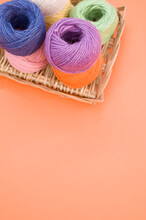 Vertical Shot Of Colorful Yarns On An Orange Background With Space For Text