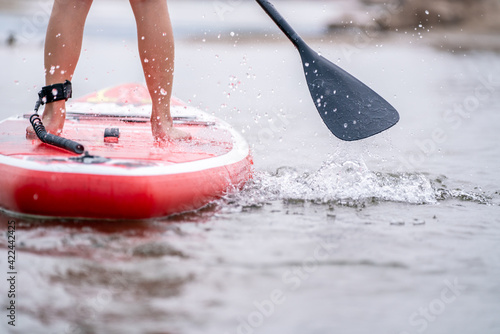 close-up of legs Stand up paddle boarding on the river.