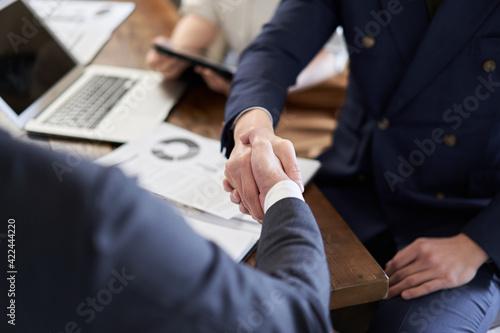握手をするアジア人ビジネスマンの手元 Fotobehang