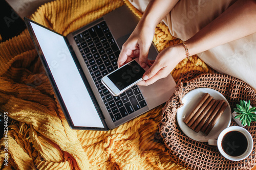 Fototapeta Top view of hand using smart phone with laptop and breakfast dish on the bed obraz
