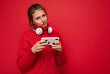 Attractive Dissatisfied Young Brunet Woman Wearing Red Sweater Isolated Over Red Background Wall Holding And Using Mobile Phone Surfing On The Internet And Wearing Bluetooth Headphones Looking At