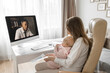 Successful business lady is working from home, having video meeting with colleague. Young mother with a small child in arms discussing work questions about project. Distant work concept