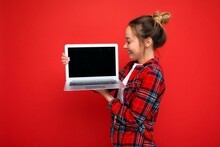 Side Profile Photo Of Charming Pretty Young Lady Holding Netbook Looking At Screen Wearing Red Shirt Isolated Over Red Wall Background