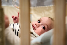 Cute Infant With Big Black Eyes At Bed.