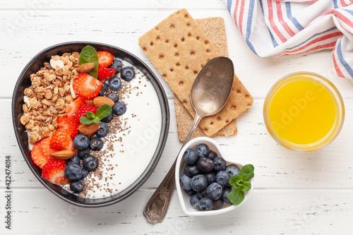 Fototapeta Healthy breakfast with bowl of granola, yogurt and fresh berries obraz