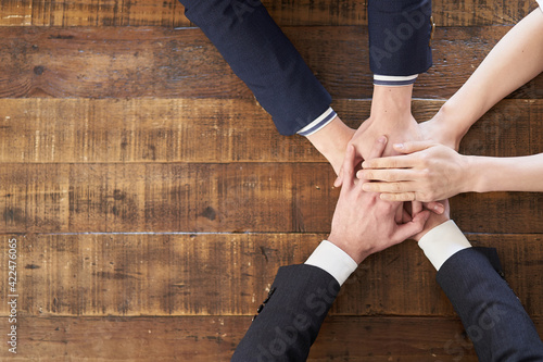 Fototapeta テーブルの上で手を重ねるアジア人ビジネスパーソン obraz