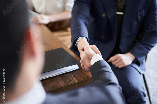 Tela 商談で握手をするアジア人ビジネスマン