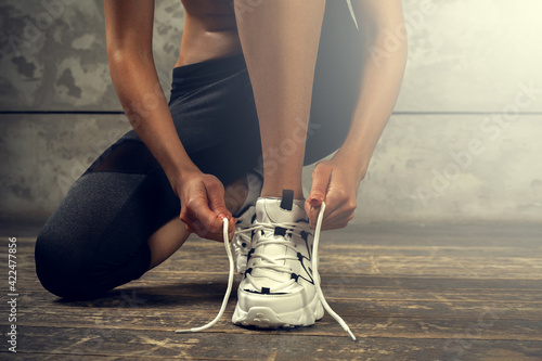 Fototapeta Sports woman hands tying shoelaces of sneaker obraz