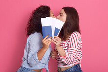 We Are Going To Trip! Girls Kissing And Covering Their Mouths With Tickets And Passports, Ladies Wearing Blue And Striped Shirts, Posing Isolated Over Pink Background.