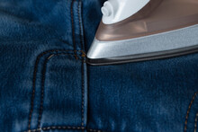 The Process Of Ironing Jeans With An Iron. Iron Spout Close-up On Denim. Routine Household Duties Of A Housewife.