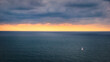 A small sailboat sails in a relaxing scene in a calm sea.