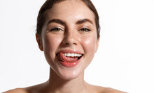 Beauty Face Of Girl Showing Perfect White Healthy Smile, Smiling With Sticked Tongue. Woman With Glowing Hydrated Clean Facial Skin, Thick Eyebrows, Nude Makeup And Naked Shoulders, White Background