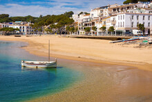 A Small Boat Is Washed Up On Llafranc Beach On A Spring Day When The Beach Is Empty. Palafrugell, Catalonia, Spain