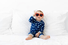 Funny Smiling Baby Sitting On White Bed With Heart Sunglasses