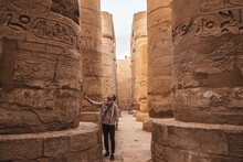 Young Man Gazing Up In Wonder At The Massive Columns At Karnak Temple In Luxor Egypt