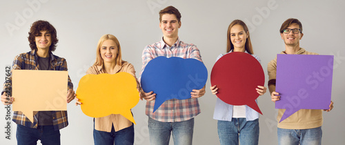 Obraz Voicing out our opinions. Young boys and girls showing on camera blank multicolored posters with speech bubble with place for text. Social media concept. Positive youth on a gray background. - fototapety do salonu