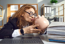 Funny Weird Looking Thrifty Man In Hilarious Round Thick Lens Glasses Sitting At Office Desk With Laptop Computer And Kissing Piggy Bank. Concept Of Loving Money And Saving Up
