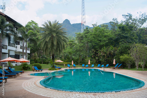Fotografia Deserted Thai hotel with a swimming pool, palm trees and sunbeds on a sunny day