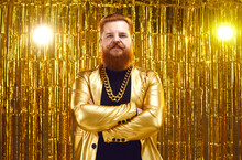 Portrait Of Bearded Guy In Funky Outfit. Serious Unfriendly Rich Young Man In Shiny Golden Disco Jacket And Gold Chain Necklace Standing Arms Folded Against Glittering Foil Fringe Curtain Background