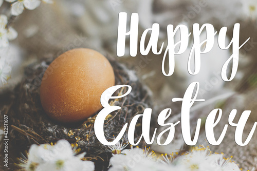 Fotografia Happy Easter text on easter egg in nest, white bunny, feathers and cherry blossoms on rustic table, handwritten sign