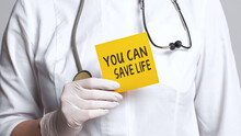 Cropped View Of Doctor In A White Coat And Sterile Gloves Holding A Note With Text - YOU CAN SAVE LIFE