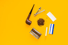 Set Of Accessories For Smoking Tobacco Top View, Smoking Pipe, Cigarette, Rolling Machine And Paper. Isolated Flat Lay On Yellow Background. Place For Text, Copy Space