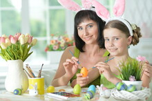 Happy Mother With Daughter Wearing Rabbit Ears Decorating  Easter Eggs