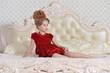 cute little girl in red dress lying on bed