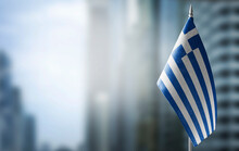 A Small Flag Of Greece On The Background Of A Blurred Background