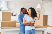 Relocation Concept. A Smiling Cheerful Multiracial Couple In Embraces Holding Keys Stating In New Apartment Among Cardboard Boxes, Bought Real Estate, Newlyweds Get A Mortgage