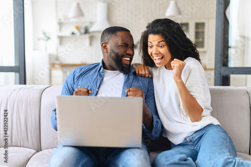 Overjoyed cheerful multiracial couple celebrating good news looking at the lapto Wallpaper Mural