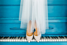 Beige Bride Shoes Standing On The Piano, Covered With A White Veil. A Pair Of Expensive And Trendy Wedding Bridal Accessories. Bright Background