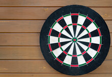 Darts Board On Brown Wooden Background.