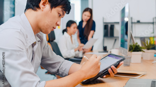 Successful executive Asia young businessman smart casual wear drawing, writing and using pen with digital tablet computer thinking of inspiration search ideas working process in modern office.