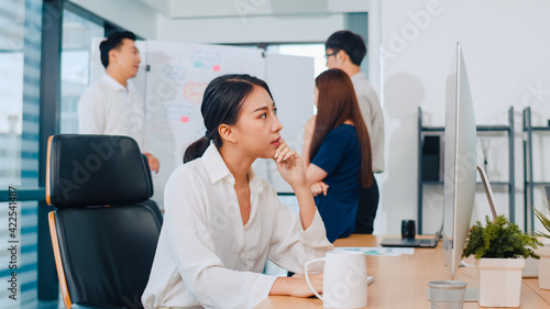 Millennial young Chinese businesswoman working stress out with project research problem on computer desktop in meeting room at small modern office. Asia people occupational burnout syndrome concept.