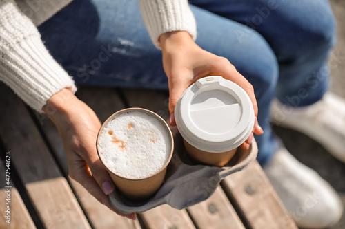Obraz Woman with takeaway cups of tasty latte outdoors, closeup - fototapety do salonu