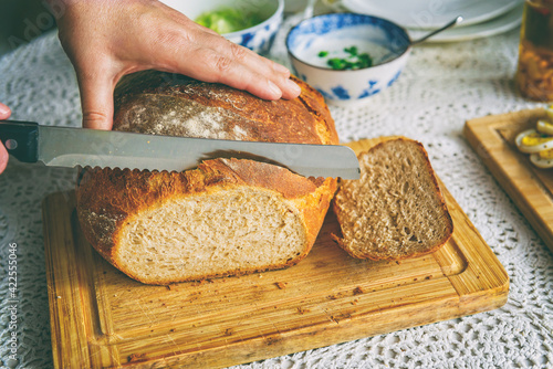 Foto Woman cuts fresh loaf of bread into slices