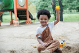 African little boy smile and enjoy playing sand with toys loader on playground outdoors in the park on a sunny day