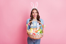 Photo Of Excited Lady Hold Easter Basket Open Mouth Wear Bunny Ears Headband Blue Pullover Isolated Pink Background