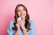 Photo Of Minded Pretty Lady Hold Telephone Look Up Empty Space Beaming Smile Wear Blue Pullover Isolated Pink Background