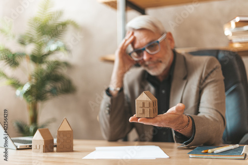 Real estate crisis. Mature man in the office at the table holding a model of the house. Financial advisor, investment and home purchase.