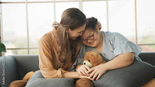 Foto Mother supporting sweet down syndrome daughter to learn and relax from the internet, embracing child to encourage down syndrome girl at home