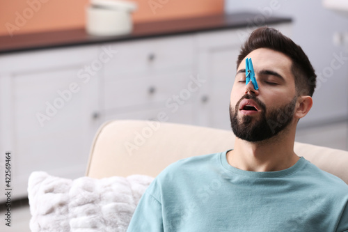 Fotografia, Obraz Man with clothespin suffering from runny nose at home