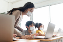 Asian Young Teacher With Little Boy In Protective Face Masks Using Laptop For  Studying In Classroom.