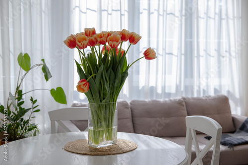 Fototapeta A bright bouquet of tulips in the interior of a light kitchen. Vase with tulips on the table. Spring flowers. Fresh orange buds. Cozy kitchen. Flowers on the background of the window obraz