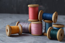 Skeins Of Colored Thread. Composition Of Sewing Thread Coils On A Gray Background. Several Reels Of Colored Thread