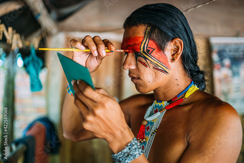 Fotografie, Obraz Indian from the Pataxó tribe, using a mirror and doing face painting