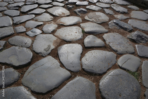 Fotografia Ancient cobblestones in Rome - Italy.